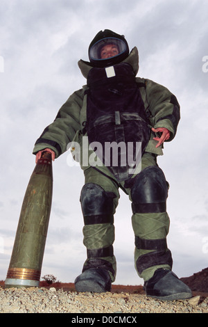 A US Marine Explosive Ordnance Disposal Specialist in Bomb Disposal Suit Palms Tip 155mm High Explosive Artillery - Stock Photo