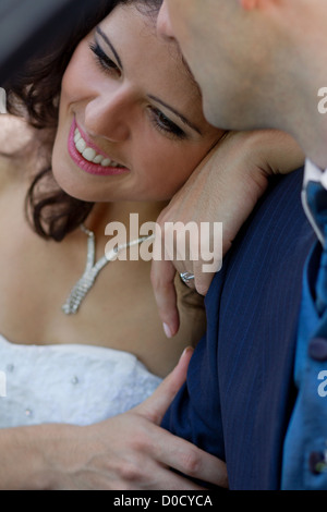 Happy young bride leaning on his strong shoulder - Stock Photo