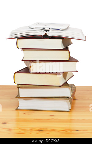 A pile of books and e-book above on wood table against a white background - Stock Photo