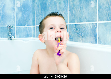 Little boy brushing his teeth in the bath tub - Stock Photo