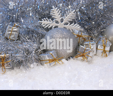 Christmas background with gifts and baubles nestled in snow - Stock Photo