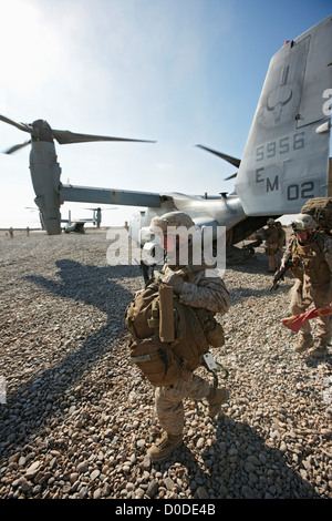 A U.S. Marine offloads gear MV-22 Osprey after landing combat outpost in Helmand Province southern Afghanistan. - Stock Photo