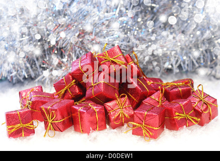 Christmas gifts in snow on a bokeh lights background - Stock Photo