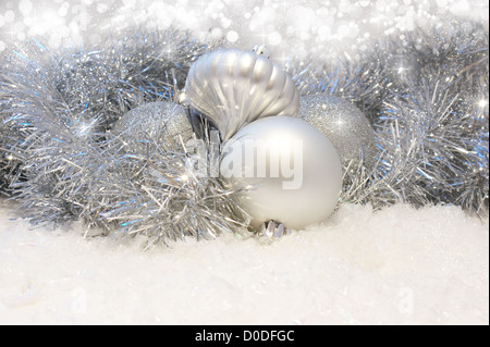 Silver Christmas baubles nestled in tinsel and snow - Stock Photo