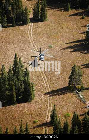Air to air view of a Sikorsky UH-60 Blackhawk hovering above a two-track dirt road high in Colorado's Rocky Mountains. - Stock Photo
