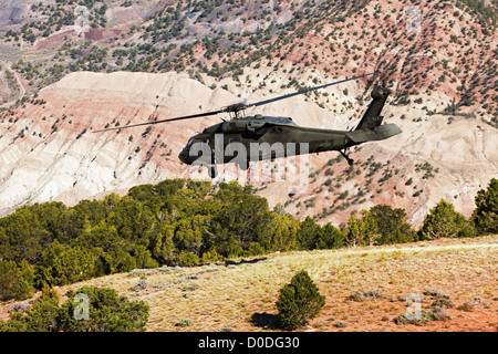 A UH-60 Blackhawk helicopter launches from a high altitude landing zone in Colorado's Rocky Mountains. - Stock Photo