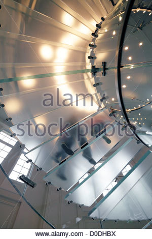 winding glass stair from under with people walking up Apple store amsterdam - Stock Photo