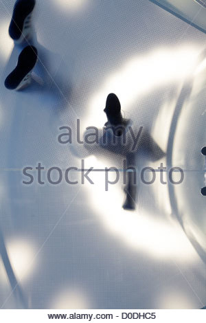 frosted glass plate with people standing on it seen from under - Stock Photo