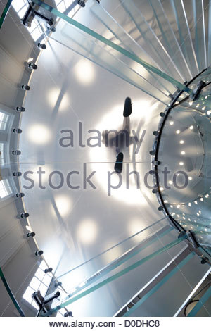 frosted glass plate with person standing on it seen from under - Stock Photo