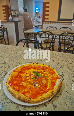 Pizza Marinara the pizza with tomato sauce garlic and basil in pizzeria along Spaccanapoli street Naples Italy - Stock Photo
