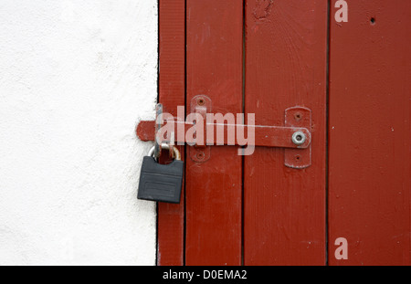 Whitewashed fishing shed with red wooden door locked with bolt and padlock. - Stock Photo