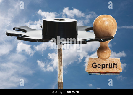 Stamp with German inscription Geprüft (certified) hangs in a stamp rack, background sky - Stock Photo
