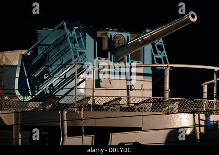 Isolated view of  a WWII Naval Gun brightly lit at night. - Stock Photo