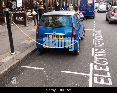 Electric car charging in street in London - Stock Photo