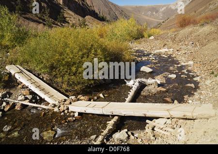 broken log bridge over McGee Creek in the Sierra Nevada - Stock Photo