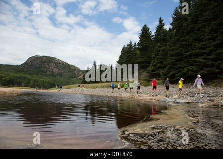 Hikers wearing colorful outdoor gear walking around a lake in Acadia National park near Bar Harbor Maine, USA - Stock Photo