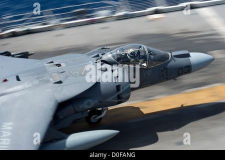 An AV-8B Harrier launches from the flight deck of the amphibious assault ship USS Bonhomme Richard - Stock Photo