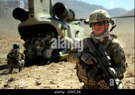 A US Army soldier secures the landing zone as his team loads a tactical vehicle into the cargo bay of a CH-47 Chinook - Stock Photo