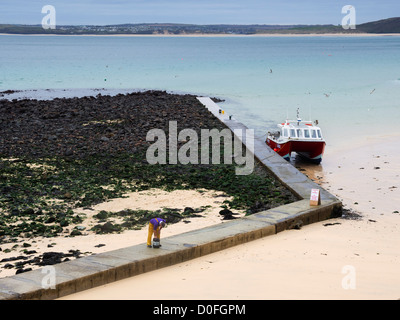 Low tide on the beach at St Ives, Cornwall. A fisherman works on his twin hulled boat on the jetty outside the main - Stock Photo