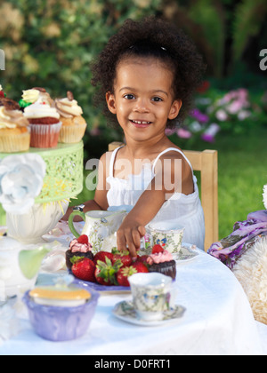 Happy smiling three year old girl having a party outdoors - Stock Photo