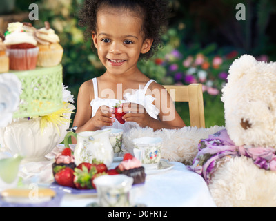 Happy smiling three year old girl having a party outdoors sitting at the table with fruits and cupcakes - Stock Photo