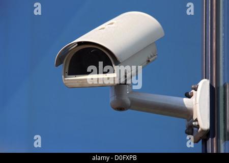 white cctv security camera on blue background - Stock Photo