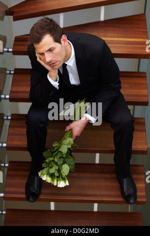 Young gentleman, sits quietly moping after having a spat with his girlfriend - Stock Photo