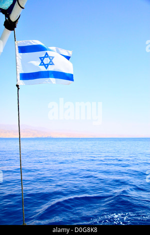 Flag of Israel on the wind, Red sea in the background - Stock Photo