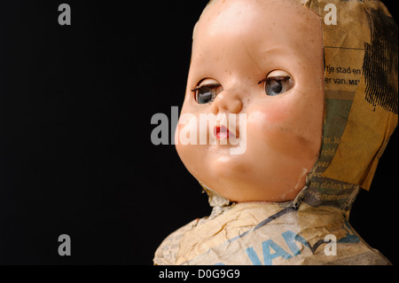 Close up of doll face on black background - Stock Photo