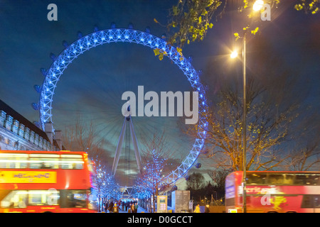 London Eye Millennium Wheel with blue Christmas Xmas lights and double-decker bus at dusk in winter, December - Stock Photo