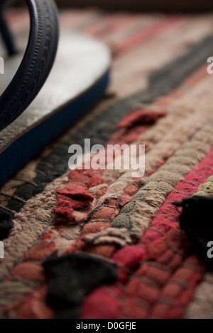 Detail of a floor mat made up of multiple pieces of cloth of different colours. Part of a flip-flop is seen on the - Stock Photo