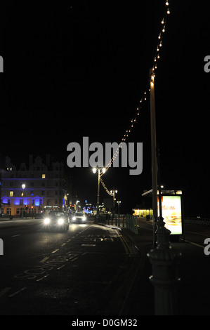 Traffic headlights on Brighton seafront at night with lights strung out UK - Stock Photo