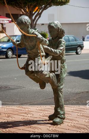 Sculpture of children playing on a swing, 'Cruce de Arinaga', [Gran Canaria]. - Stock Photo