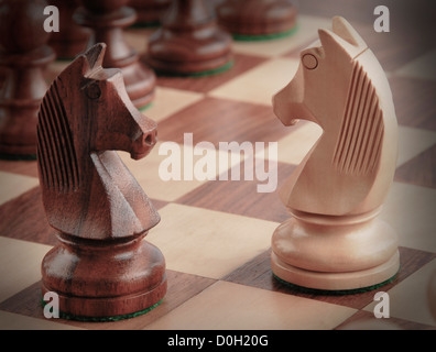 Knights facing each other on a chess board - Stock Photo