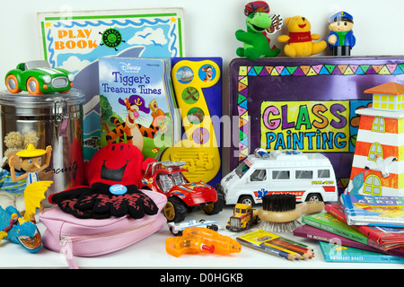 Assorted Childrens soft toys on shelf including miniature cars, teddy bear, gloves, books - Stock Photo