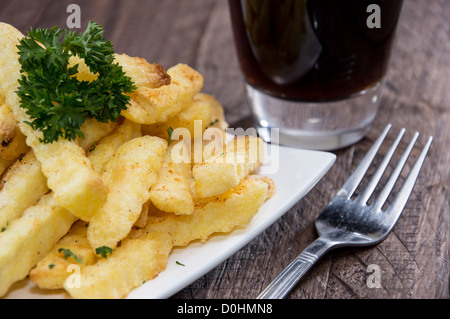 Plate with french fries on wooden background - Stock Photo