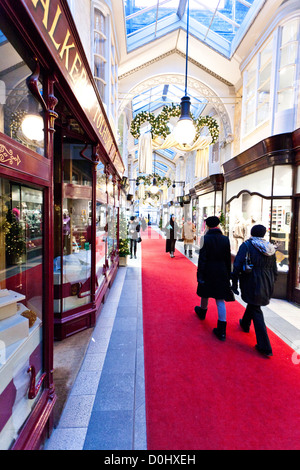 Christmas decorations and shoppers in the Burlington Arcade in London. - Stock Photo