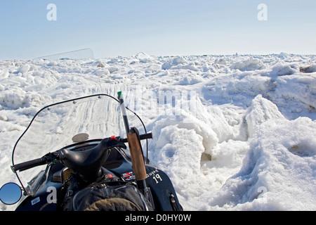 Snowmobile and shotgun on Arctic ice, Barrow, Alaska - Stock Photo
