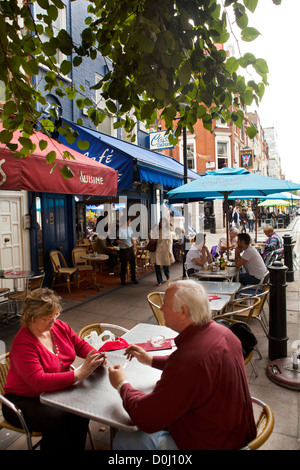 A view of a couple of people sitting at a table at a street cafe in the City of London. - Stock Photo