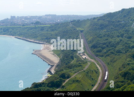 Train passing along the Kent coastline viewed from the cliffs above Folkestone Warren in Kent. - Stock Photo