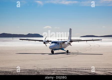 View of an aircraft taxiing across the beach after landing at Barra Airport. - Stock Photo
