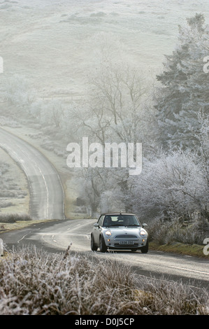A mini car drives along a mountain road in the Wye Valley. - Stock Photo
