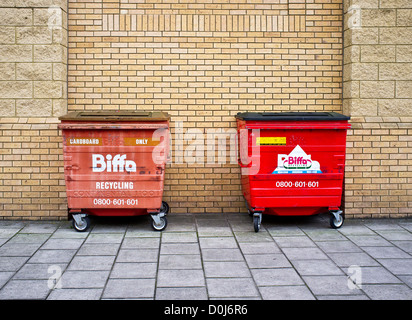 Two recycling bins against a brick wall. - Stock Photo