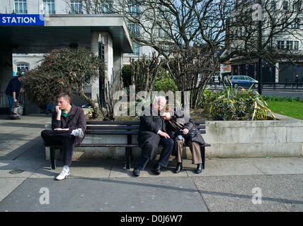 A couple sleeping on a bench in London. - Stock Photo