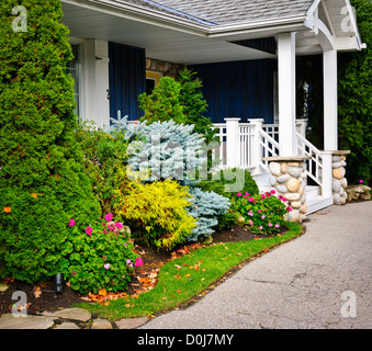 Front entrance of house with garden and porch - Stock Photo