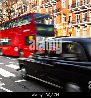 A red London bus and Black Cab Taxi approach the famous Abbey Road pedestrian crossing made famous by the cover - Stock Photo