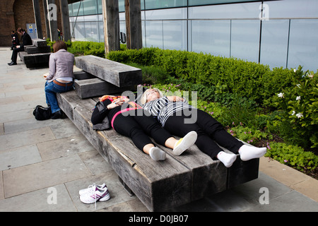 People dozing on a bench in The City. - Stock Photo