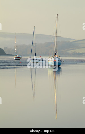 Small boats on the still estuary at dawn near Kingsbridge in Devon. - Stock Photo