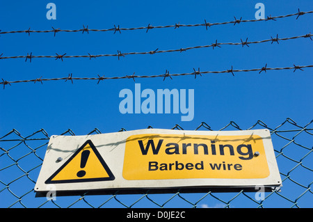 Warning sign on a barbed wire fence against bright blue sky. - Stock Photo