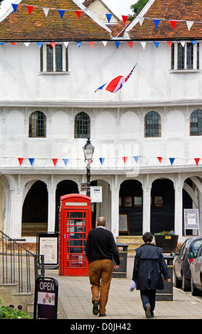 Tourists walk towards the 15th Century Guildhall in Thaxted. - Stock Photo